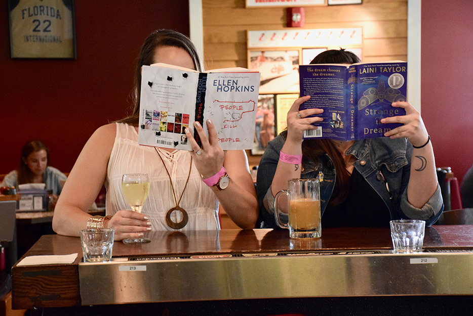 Yesenia and Jackie reading books at the bar
