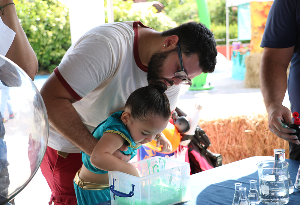 Father holding daughter to touch slime