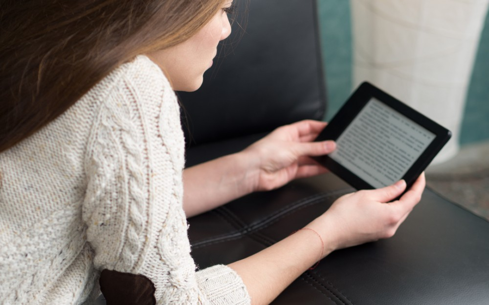 girl reading through a kindle