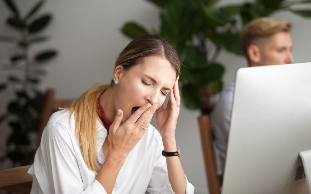Woman yawning while working.