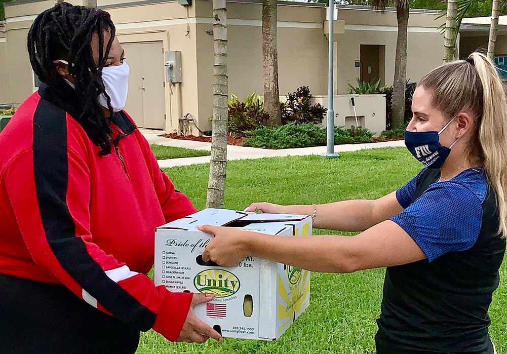 Kandys handing box of food to student