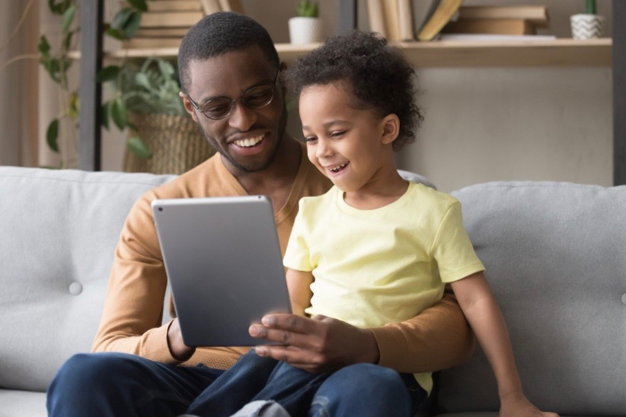 father and son looking at tablet