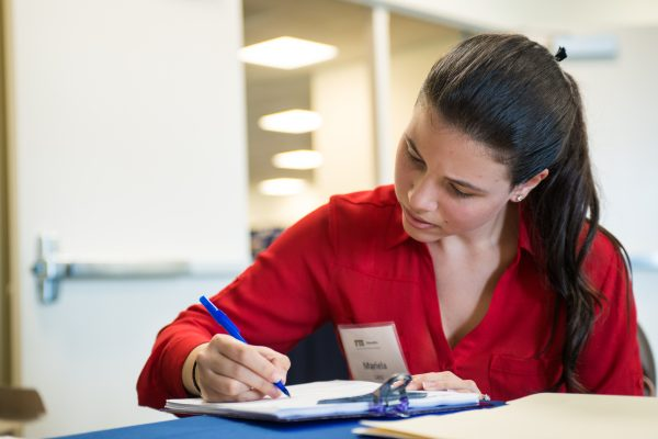Person writing down information on a clipboard