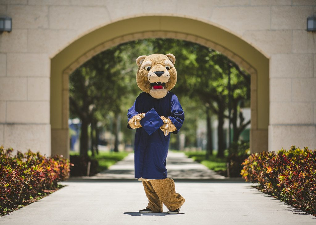 Roary, FIU mascot, wearing graduation gown and posing with the cap in the middle