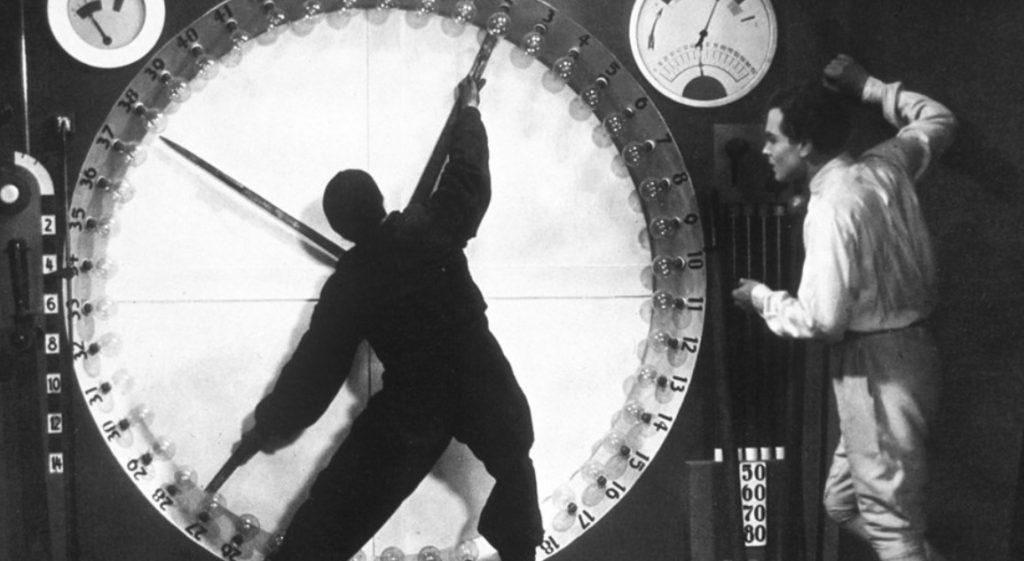 Man standing next to clock; movie clip