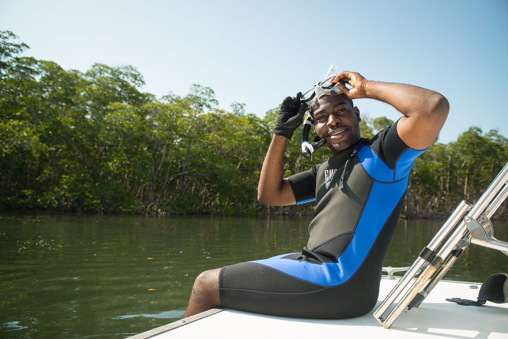 Person sitting on a boat with wetsuit on and snorkeling gear on head looking at camera