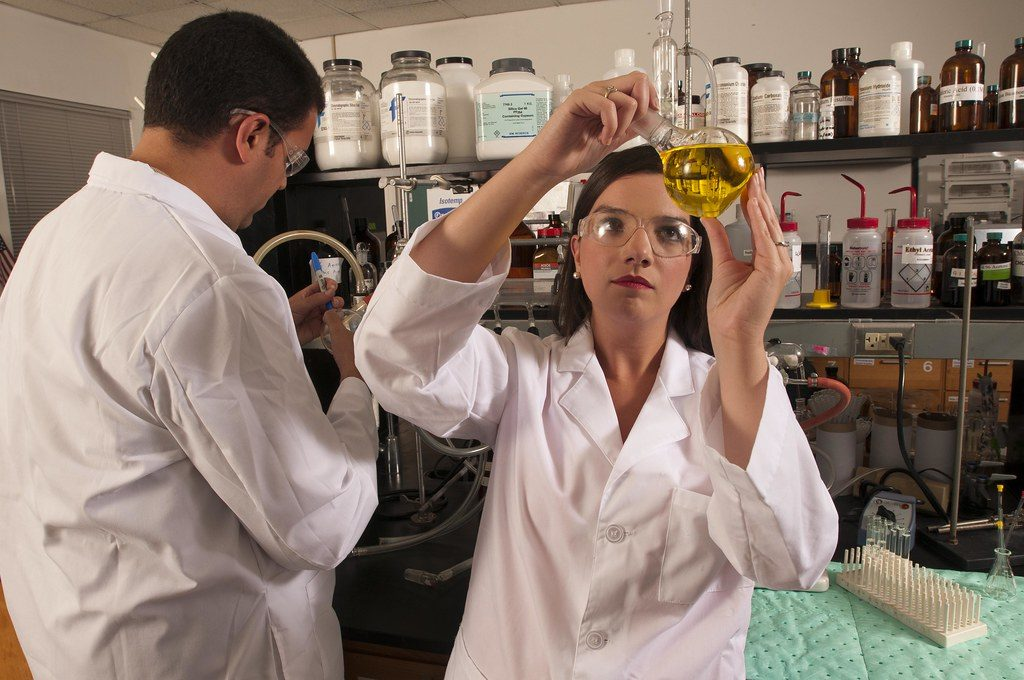 Two people in a laboratory. On the left, a person labeling a specimen. On the right, a person looking at a specimen.