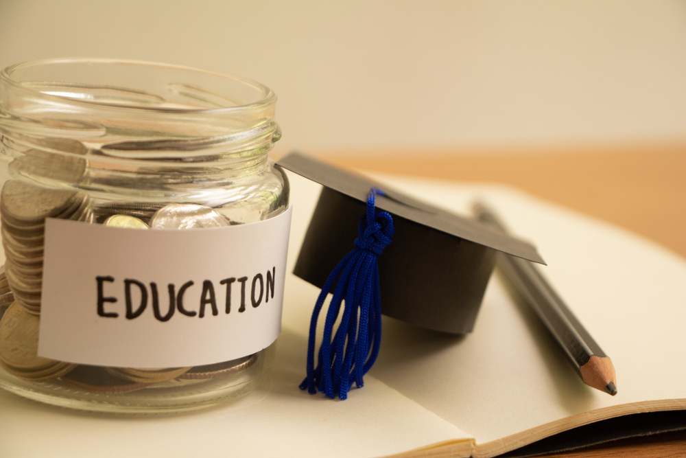 Graduation hat with glass jar saving money scholarship for education in future on wood table