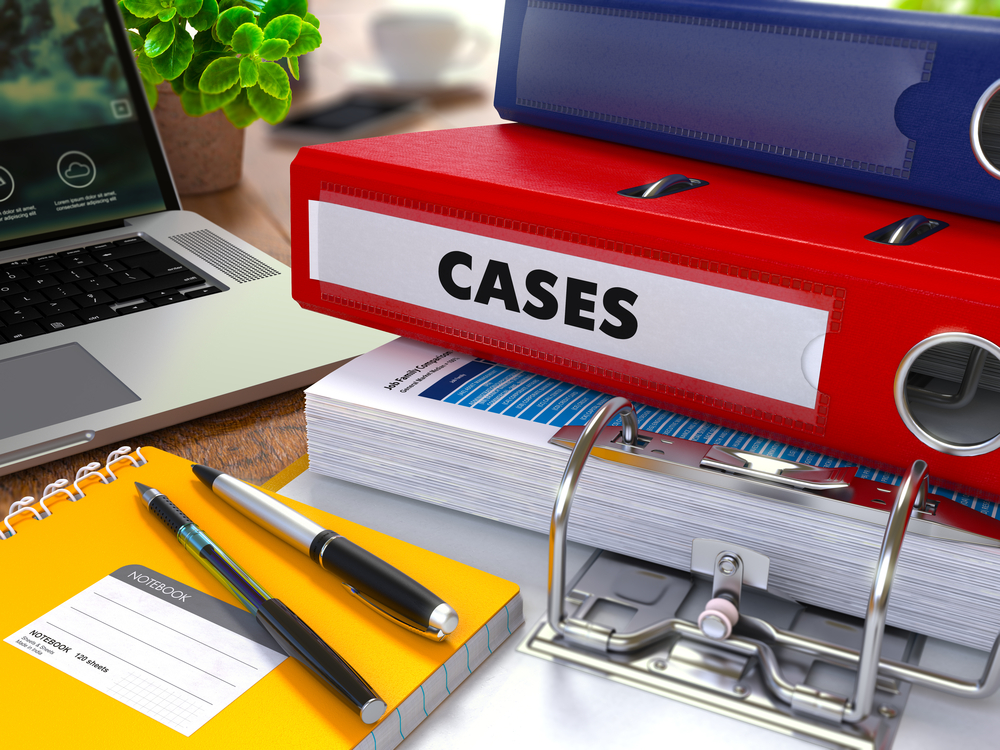 Picture showing binder with the word cases on it next to a laptop and notebook with pens.