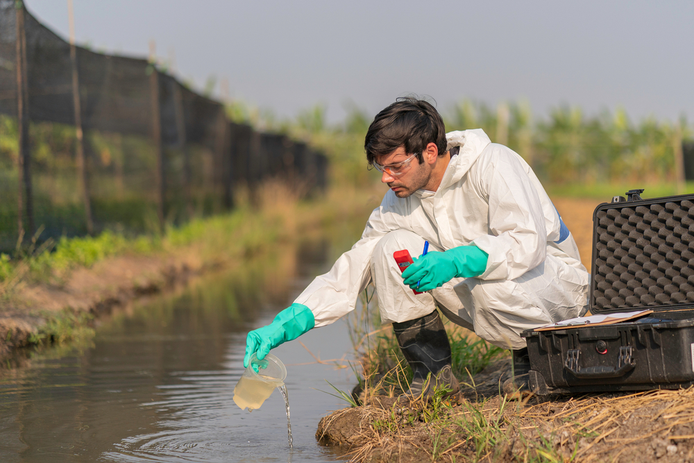 Scientist in protective gear collecting sample of water from canal.
