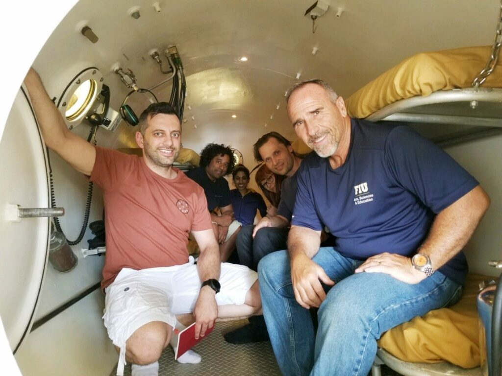 Course Instructor, Roger Garcia, and students inside recompression chamber