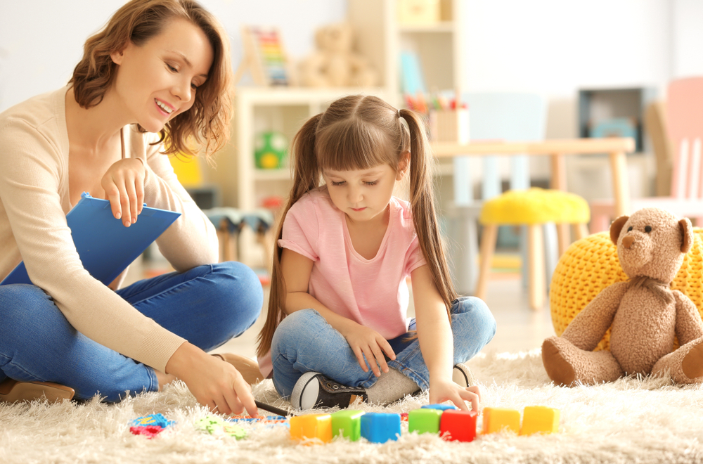 Person and child playing with toys on rug.