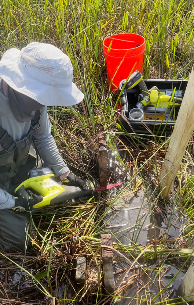 Travieso uses power tools to repair a structure in the Everglades.