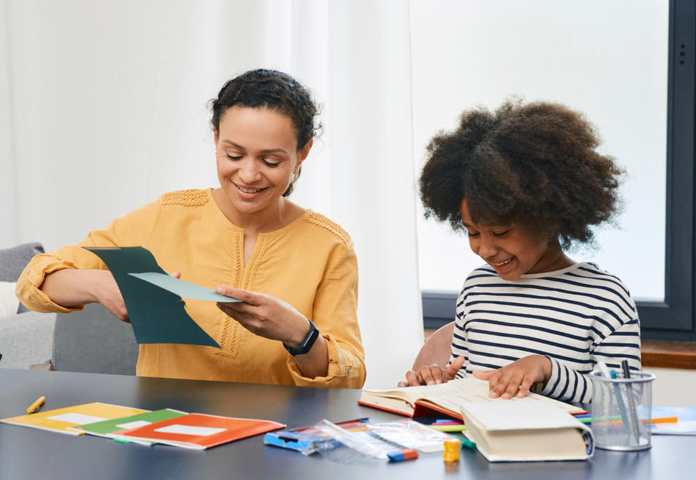 Person sitting next to child doing craft activities